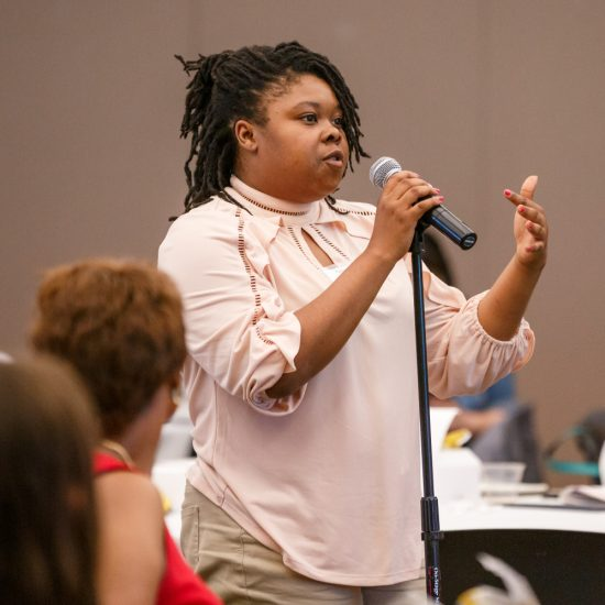 A person speaks from a microphone at the 2019 UIC Minority Health Conference.