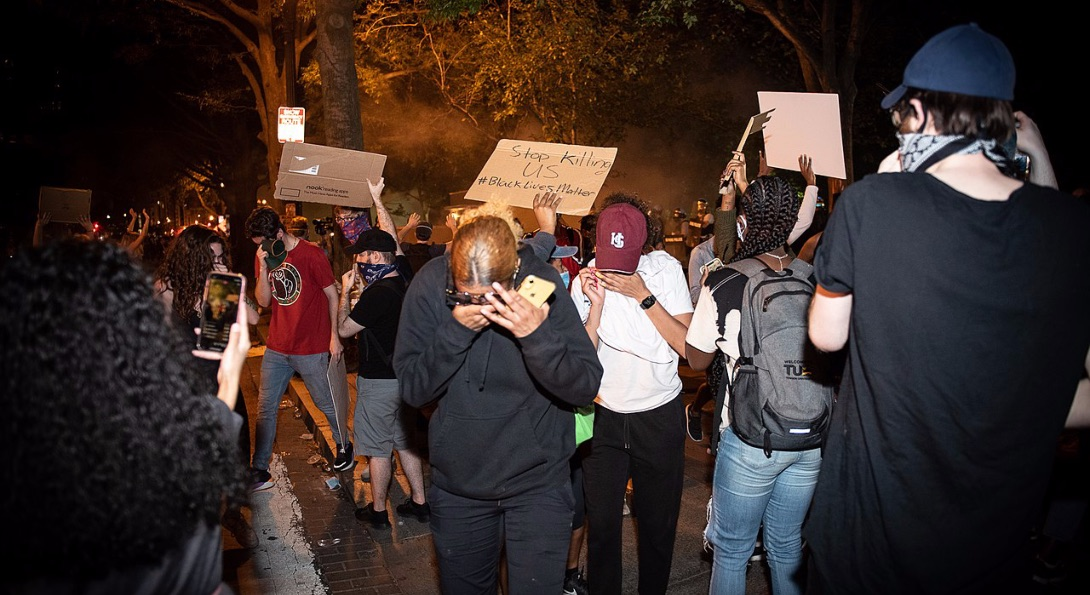 Protestors wipe their eyes after tear gas was deployed by police at a George Floyd protest in Washington DC.