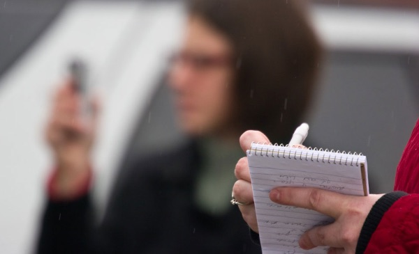 A person writes in a reporter's notebook.